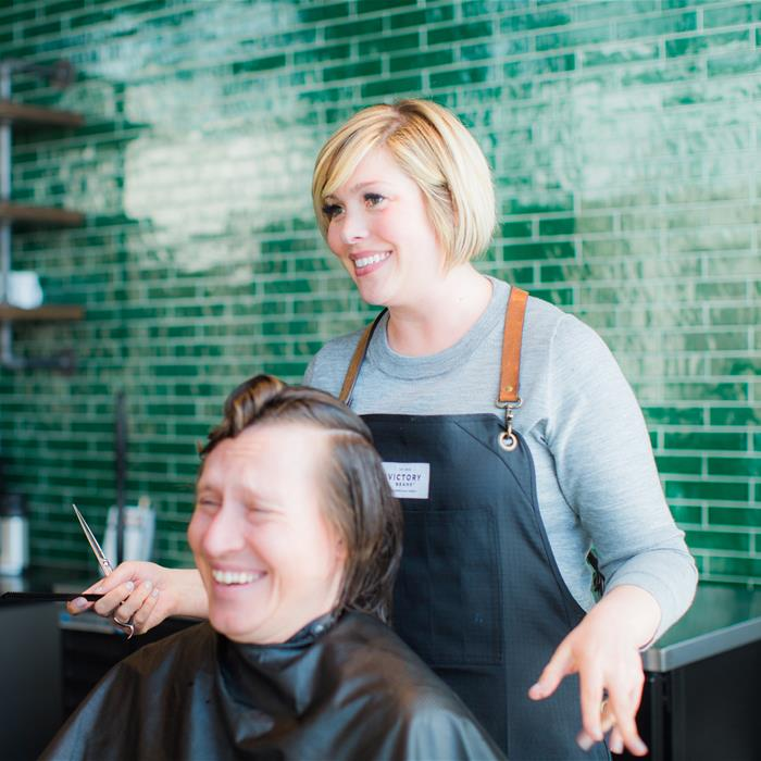 A hairstylist and her client smiling